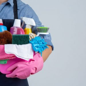 young-girl-is-holding-cleaning-product-gloves-rags-basin-white-wall
